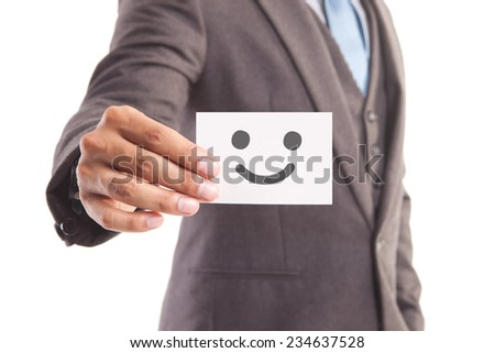 Businessman hand showing someone his business card with Smiley face - stock photo