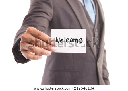 "Businessman hand showing someone his business card with""welcome"" message"