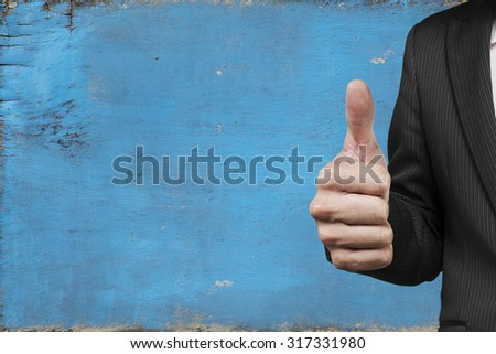 Businessman hand showing thumb up, with old blue noticeboard background. - stock photo