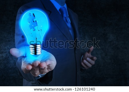 businessman hand shows light and puzzle partnership - stock photo