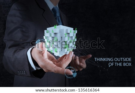 businessman hand shows word thinking outside the box as concept