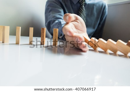businessman hand stop dominoes continuous toppled or risk with copy space