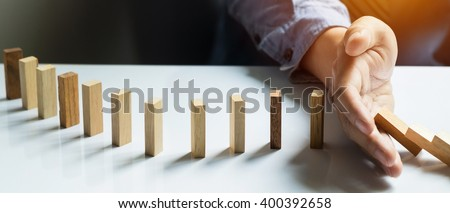 businessman hand stop dominoes continuous toppled, Panoramic composition suitable for banners