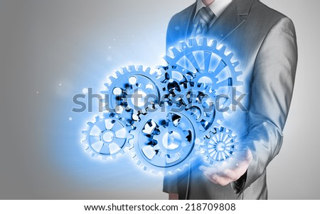 businessman hand touch blue gear to success as concept