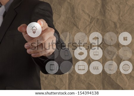 businessman hand touch graphic icon light bulb with crumpled recycle paper background as concept - stock photo