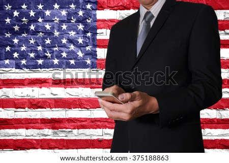 Businessman hand touch screen smart phone and brick Walls are painted United States (USA) flag background as business, communication with mighty nation concept.