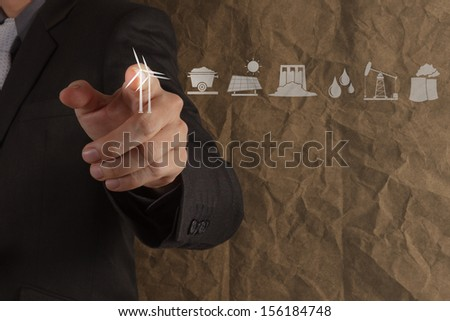 businessman hand touch Wind turbines on crumpled recycle paper background as concept - stock photo