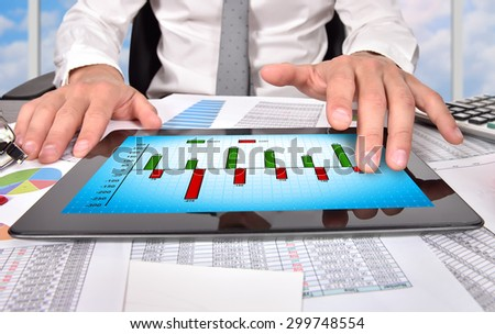 businessman hand touching digital tablet with chart of profit and cost - stock photo