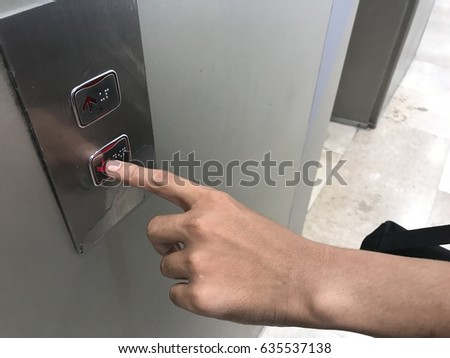 Businessman hand touching going down sign on lift control panel
