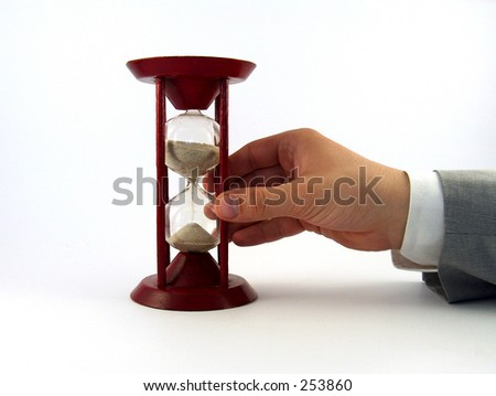 businessman hand turning a sand glass - stock photo