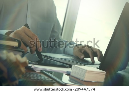 Businessman hand using laptop and mobile phone with overcast effect on wooden desk as concept with social media diagram - stock photo