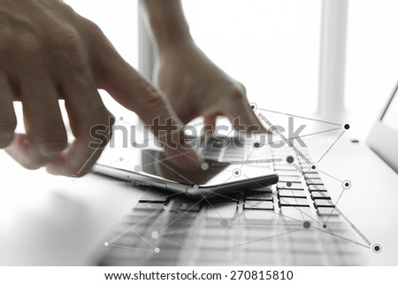 Businessman hand using laptop and mobile phone with social network diagram on wooden desk as concept - stock photo