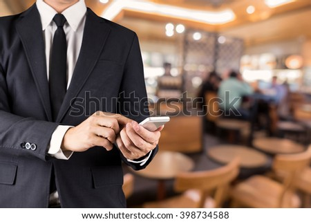 Businessman hand Using Smartphone in cafe .Lifestyle technology concept - stock photo