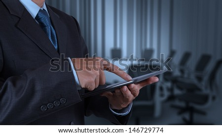 businessman hand using tablet computer and board room background - stock photo