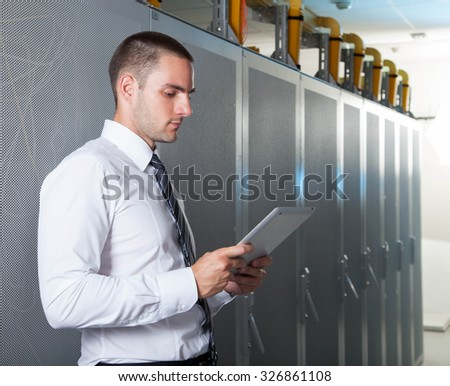 businessman hand using tablet computer and server room - stock photo