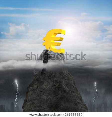 Businessman hand wanting for golden euro symbol on mountain peak high in the sky with opposite weather conditions background, sunny sky cloudscape, dark overcast lightning raining cityscape - stock photo