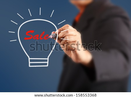 businessman hand with a pen drawing light bulb inside is sale - stock photo