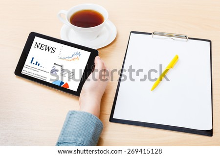 businessman hand with tablet PC with business news on screen at office table - stock photo