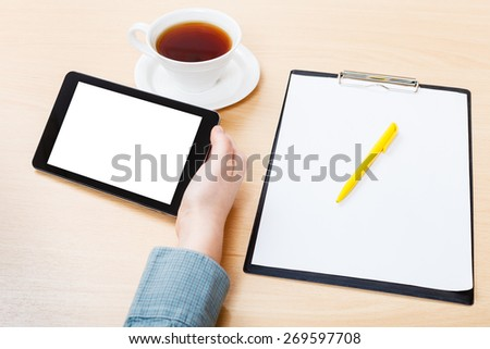 businessman hand with tablet PC with cutout screen at office desk - stock photo