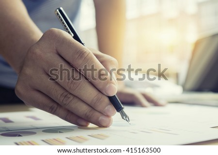 businessman hand working and discussing the charts and graphs,businessmen using Notebook and writing business plan at meeting,business concept,teamwork,vintage color,selective focus,with copy space