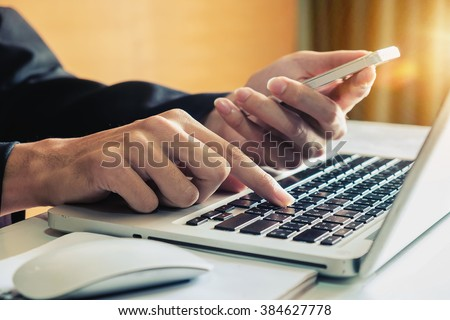 Businessman hand working and smart phone and laptop on wooden desk in office in morning light. vintage effect