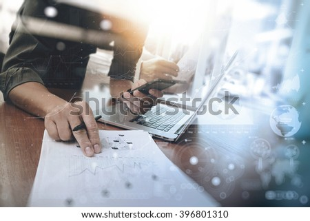 businessman hand working on laptop computer with digital layer business graph information diagram on wooden desk as concept   - stock photo