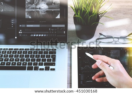 businessman hand working stylus pen and digital tablet computer and memo note and laptop computer.strategy layer effect. Attending video conference in modern office.On wooden desk
