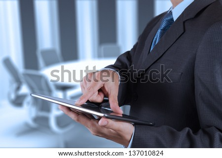 Businessman hand working with a digital tablet on meeting room background - stock photo