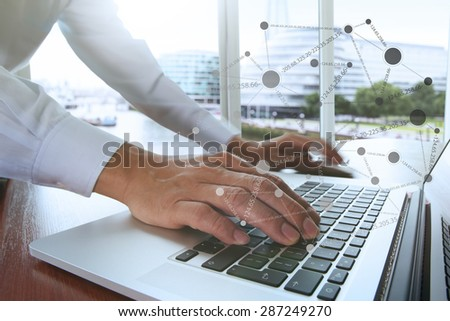 businessman hand working with business documents on office table with laptop computer and london city blurred background with social media diagram - stock photo