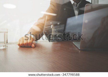 businessman hand working with modern technology and glass of water as business strategy concept - stock photo