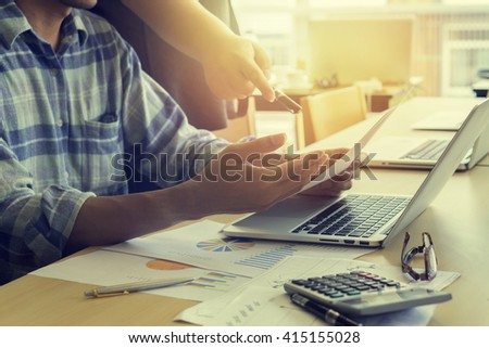 businessman hand working with new modern computer and business strategy as concept,Young creative team working together,Business people discussing charts, graphs,teamwork,vintage color,selective focus - stock photo