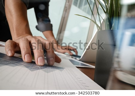 businessman hand working with new modern computer and business strategy documents with glass of water and green plant foreground on wooden desk in office