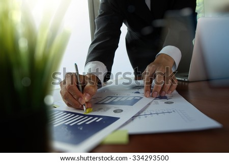 businessman hand working with new modern computer and business strategy documents with green plant foreground on wooden desk in office - stock photo