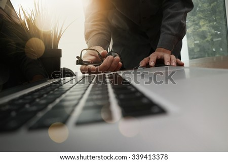 businessman hand working with new modern computer and smart phone and business strategy on wooden desk as concept