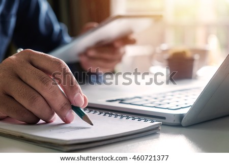 businessman hand working with new modern computer, tablet  and writing on the notepad strategy diagram as concept morning light