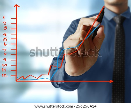 businessman hand writing a business graph on a glass wall  - stock photo