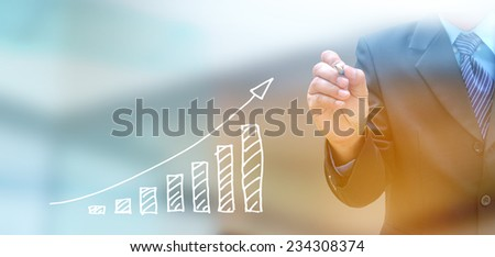 businessman hand writing a business graph on a touch screen interface  - stock photo