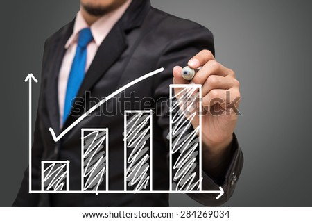 Businessman hand writing a graph on gray background, Business investment concept