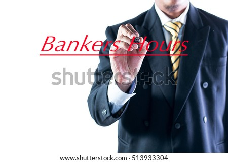 Businessman hand writing Bankers Hours on transparent wipe board.