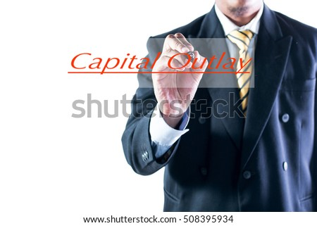 Businessman hand writing Capital Outlay on transparent wipe board.