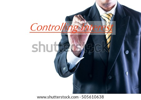 Businessman hand writing Controlling Interest on transparent wipe board.