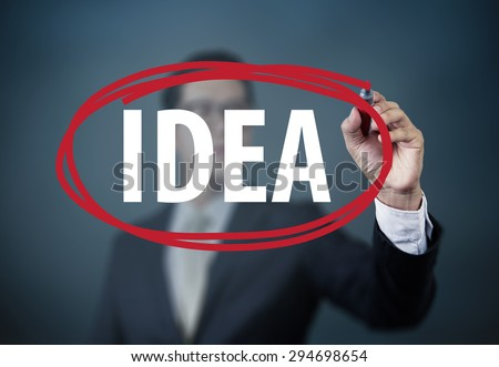 "Businessman hand writing ""Idea"" with red marker on transparent board, new business concept, studio shot - stock photo"