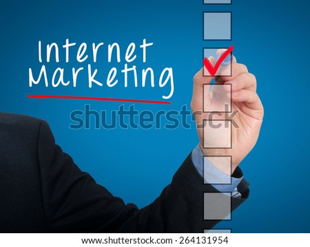 Businessman hand writing Internet Marketing and check listing task. Isolated on blue background. Stock photo