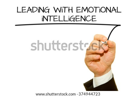 Businessman hand writing Leading with Emotinal intelligence on a transparent wipe board