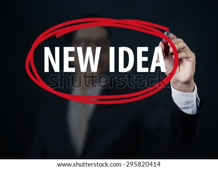 "Businessman hand writing ""NEW IDEA"" with red marker on transparent board, new business concept, studio shot - stock photo"