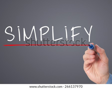 Businessman hand writing Simplify with marker on transparent wipe board isolated on grey. Stock Image - stock photo