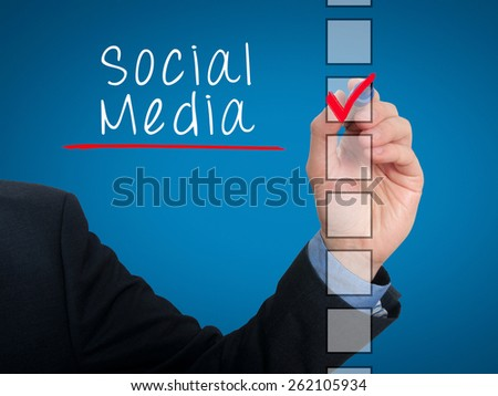 Businessman hand writing Social Media and check listing task. Isolated on blue background. Stock photo