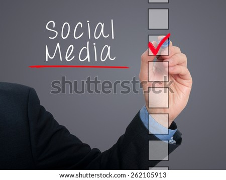 Businessman hand writing Social Media and check listing task. Isolated on grey background. Stock photo
