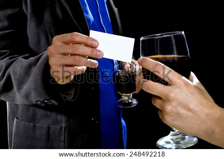 businessman handing over business card to a female at a bar - stock photo