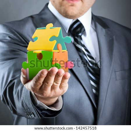 Businessman handling colorful puzzle house - stock photo